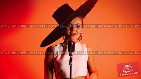Купить «An attractive woman in big retro hat singing on the stage on orange background.», видеоролик № 29537599, снято 10 декабря 2018 г. (c) Константин Шишкин / Фотобанк Лори