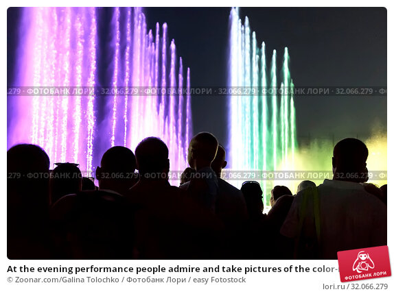 At the evening performance people admire and take pictures of the color-music fountain. Стоковое фото, фотограф Zoonar.com/Galina Tolochko / easy Fotostock / Фотобанк Лори