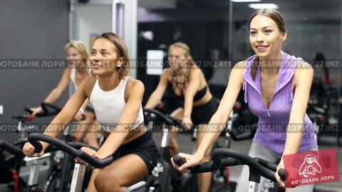 Купить «Athletic young girls during workout on stationary bicycle in fitness gym», видеоролик № 27092411, снято 28 июля 2017 г. (c) Яков Филимонов / Фотобанк Лори