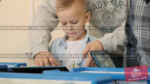Купить «Attentive teacher explains to the young blond boy how to make the robot cat from plastic details and using new technologies slow motion», видеоролик № 31004547, снято 4 августа 2020 г. (c) Denis Mishchenko / Фотобанк Лори