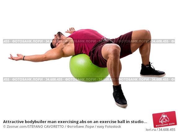 Attractive bodybuiler man exercising abs on an exercise ball in studio... Стоковое фото, фотограф Zoonar.com/STEFANO CAVORETTO / easy Fotostock / Фотобанк Лори