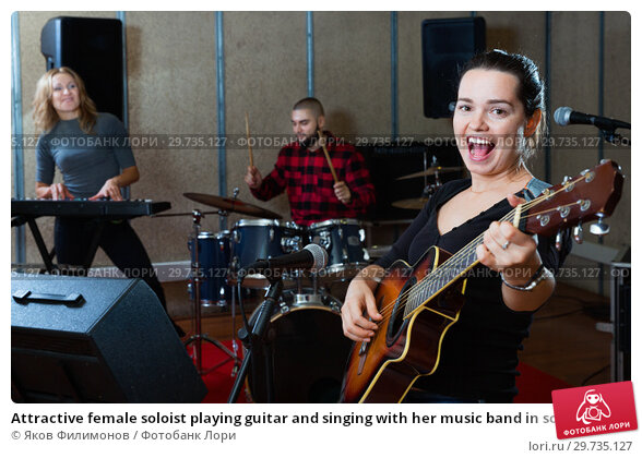Купить «Attractive female soloist playing guitar and singing with her music band in sound studio», фото № 29735127, снято 26 октября 2018 г. (c) Яков Филимонов / Фотобанк Лори