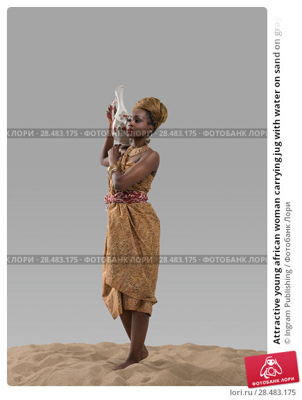Купить «Attractive young african woman carrying jug with water on sand on gray studio background», фото № 28483175, снято 1 декабря 2014 г. (c) Ingram Publishing / Фотобанк Лори