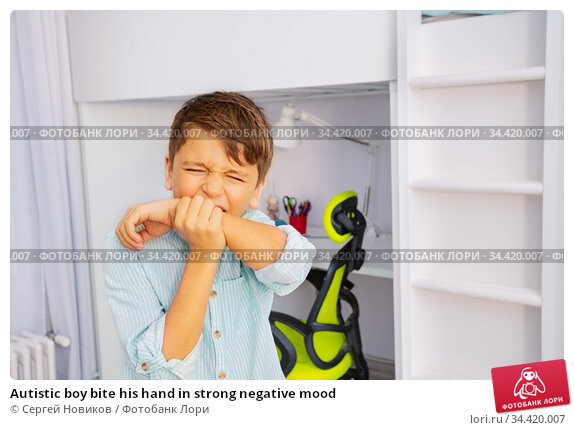 Autistic boy bite his hand in strong negative mood. Стоковое фото, фотограф Сергей Новиков / Фотобанк Лори