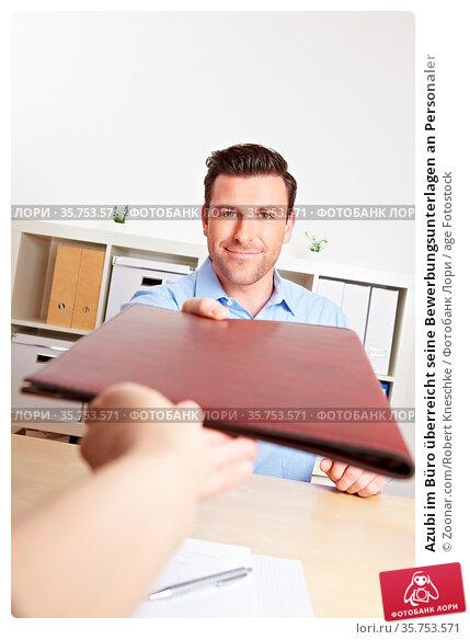 Azubi im Büro überreicht seine Bewerbungsunterlagen an Personaler. Стоковое фото, фотограф Zoonar.com/Robert Kneschke / age Fotostock / Фотобанк Лори