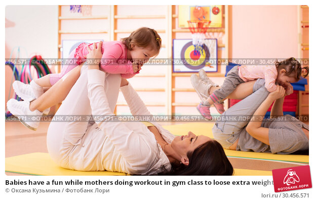 Babies have a fun while mothers doing workout in gym class to loose extra weight. Child-friendly fitness for women with kids toddlers. Lifestyle concept of parent activity with children. Стоковое фото, фотограф Оксана Кузьмина / Фотобанк Лори