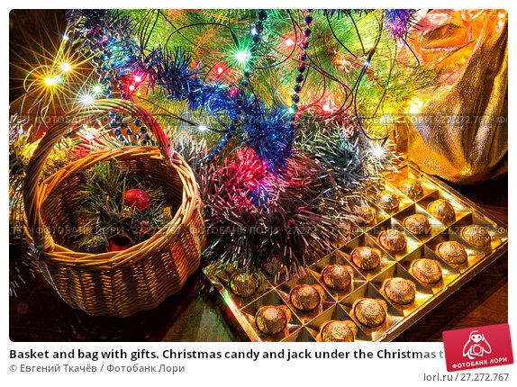 Купить «Basket and bag with gifts. Christmas candy and jack under the Christmas tree», фото № 27272767, снято 19 января 2016 г. (c) Евгений Ткачёв / Фотобанк Лори