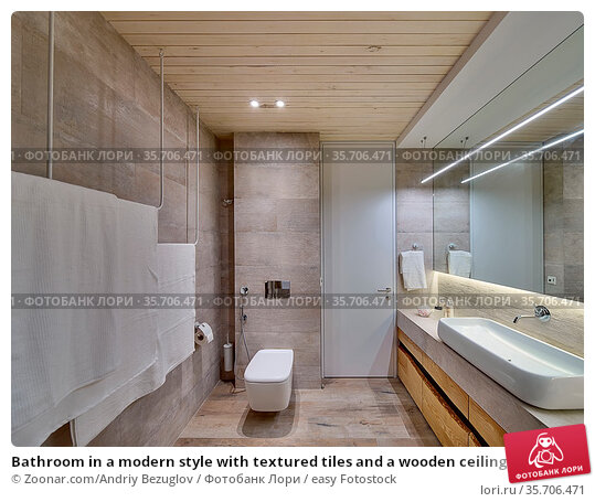 Bathroom in a modern style with textured tiles and a wooden ceiling... Стоковое фото, фотограф Zoonar.com/Andriy Bezuglov / easy Fotostock / Фотобанк Лори