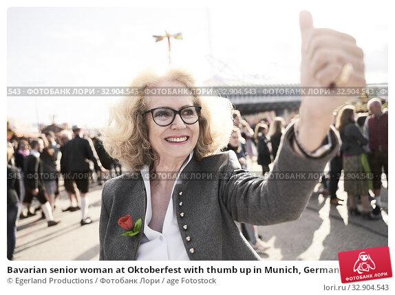 Bavarian senior woman at Oktoberfest with thumb up in Munich, Germany. Стоковое фото, фотограф Egerland Productions / age Fotostock / Фотобанк Лори