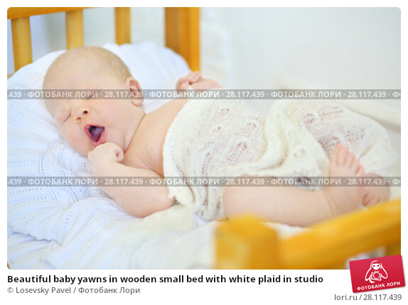 Купить «Beautiful baby yawns in wooden small bed with white plaid in studio», фото № 28117439, снято 27 августа 2016 г. (c) Losevsky Pavel / Фотобанк Лори