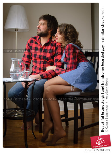 Beautiful brunette girl and handsome bearded guy in similar checkered red shirts look at each other and smile during celebration St. Valentine Day. Стоковое фото, фотограф Ольга Балынская / Фотобанк Лори