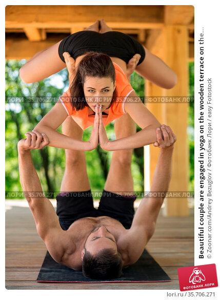Beautiful couple are engaged in yoga on the wooden terrace on the... Стоковое фото, фотограф Zoonar.com/Andrey Bezuglov / easy Fotostock / Фотобанк Лори