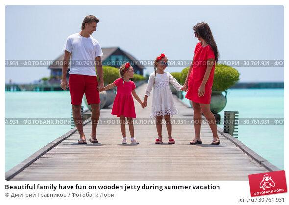 Купить «Beautiful family have fun on wooden jetty during summer vacation», фото № 30761931, снято 5 апреля 2015 г. (c) Дмитрий Травников / Фотобанк Лори