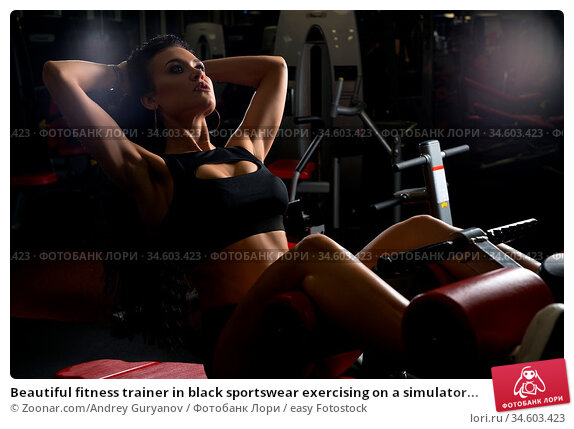 Beautiful fitness trainer in black sportswear exercising on a simulator... Стоковое фото, фотограф Zoonar.com/Andrey Guryanov / easy Fotostock / Фотобанк Лори