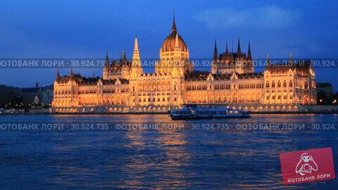 Купить «Beautiful night view of the Hungarian Parliament building and the Danube river with lights in the water in Budapest, Hungary», видеоролик № 30924735, снято 3 июня 2019 г. (c) Яна Королёва / Фотобанк Лори
