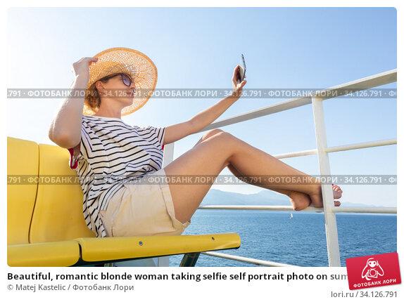 Купить «Beautiful, romantic blonde woman taking selfie self portrait photo on summer vacations traveling by cruse ship ferry boat.», фото № 34126791, снято 30 июня 2020 г. (c) Matej Kastelic / Фотобанк Лори