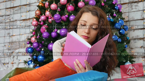 Купить «Beautiful sexy woman with Xmas tree in background reading a book lying on bright pillows. Portrait of girl posing pretty. Attractive brunette female relaxing», видеоролик № 29437655, снято 17 ноября 2018 г. (c) Ольга Балынская / Фотобанк Лори