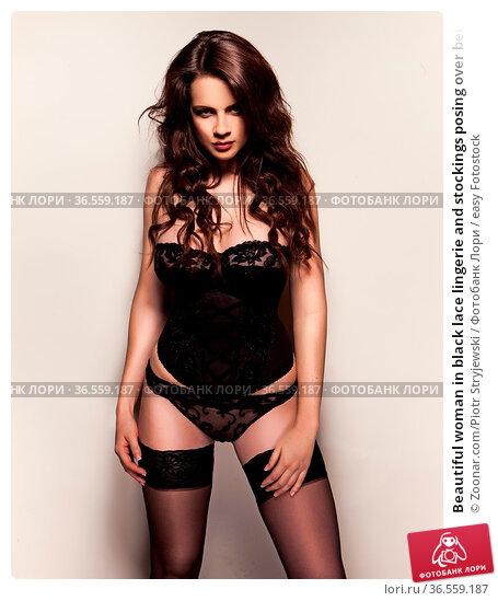 Beautiful woman in black lace lingerie and stockings posing over beige... Стоковое фото, фотограф Zoonar.com/Piotr Stryjewski / easy Fotostock / Фотобанк Лори