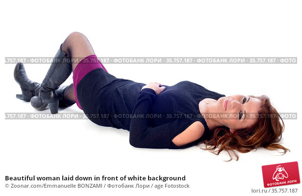 Beautiful woman laid down in front of white background. Стоковое фото, фотограф Zoonar.com/Emmanuelle BONZAMI / age Fotostock / Фотобанк Лори