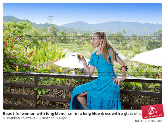 Beautiful woman with long blond hair in a long blue dress with a glass of sparkling wine sitting on the railing of the balcony against the tropics. Стоковое фото, фотограф Куликов Константин / Фотобанк Лори