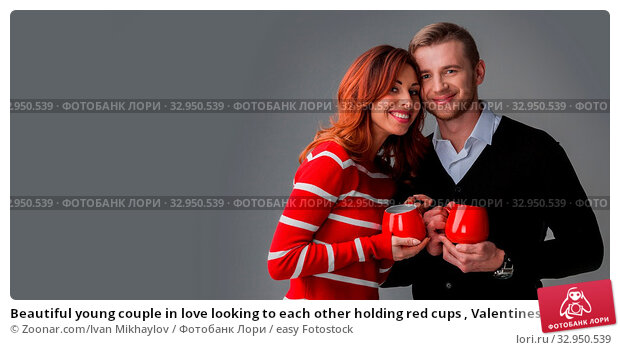 Beautiful young couple in love looking to each other holding red cups , Valentines day concept. Стоковое фото, фотограф Zoonar.com/Ivan Mikhaylov / easy Fotostock / Фотобанк Лори