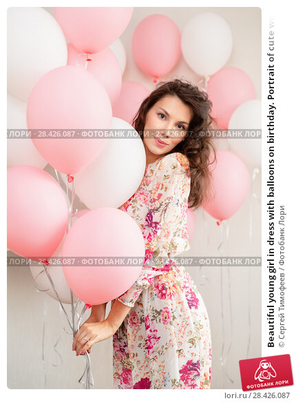 Купить «Beautiful young girl in dress with balloons on birthday. Portrait of cute woman with multicolored balloon. Cute brunette girl in the studio with balls filled», фото № 28426087, снято 29 апреля 2018 г. (c) Сергей Тимофеев / Фотобанк Лори
