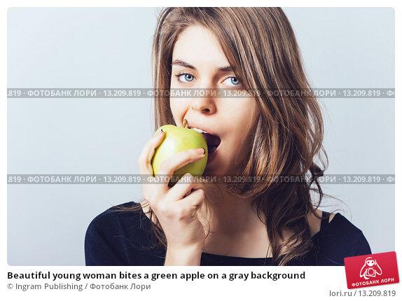 Купить «Beautiful young woman bites a green apple on a gray background», фото № 13209819, снято 23 апреля 2015 г. (c) Ingram Publishing / Фотобанк Лори
