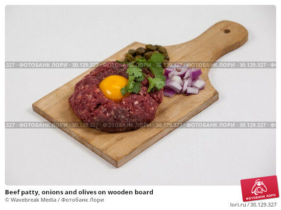 Купить «Beef patty, onions and olives on wooden board», фото № 30129327, снято 20 сентября 2016 г. (c) Wavebreak Media / Фотобанк Лори