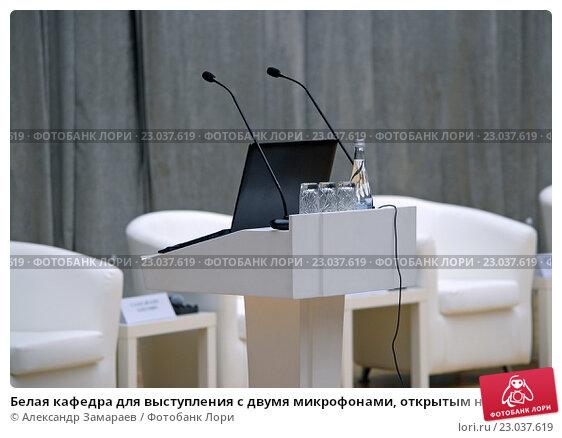 Купить «Белая кафедра для выступления с двумя микрофонами, открытым ноутбуком и стаканами на фоне кресел президиума на сцене», фото № 23037619, снято 2 июня 2016 г. (c) Александр Замараев / Фотобанк Лори