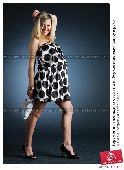 Беременная женщина стоит на каблуках и держит кепку в руке, фото № 314475, снято 3 июня 2008 г. (c) Артем Костров / Фотобанк Лори