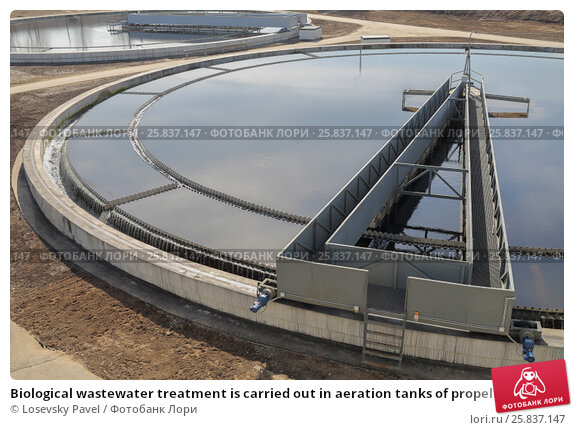 Купить «Biological wastewater treatment is carried out in aeration tanks of propellant. Along rails in circle rotates sludge scraper - it separates sludge, primary settler», фото № 25837147, снято 19 марта 2015 г. (c) Losevsky Pavel / Фотобанк Лори
