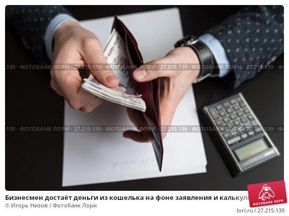 Купить «Бизнесмен достаёт деньги из кошелька на фоне заявления и калькулятора», эксклюзивное фото № 27215139, снято 6 ноября 2017 г. (c) Игорь Низов / Фотобанк Лори