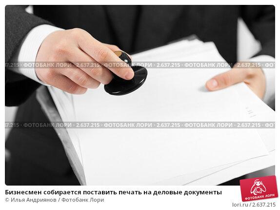 Бизнесмен собирается поставить печать на деловые документы. Стоковое фото, фотограф Илья Андриянов / Фотобанк Лори
