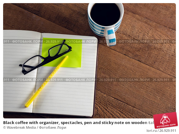 Black coffee with organizer, spectacles, pen and sticky note on wooden table, фото № 26929911, снято 26 мая 2017 г. (c) Wavebreak Media / Фотобанк Лори