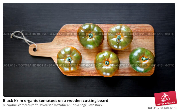 Black Krim organic tomatoes on a wooden cutting board. Стоковое фото, фотограф Zoonar.com/Laurent Davoust / age Fotostock / Фотобанк Лори