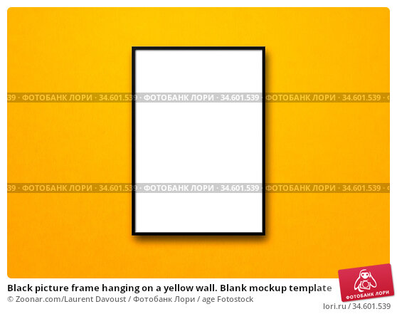 Black picture frame hanging on a yellow wall. Blank mockup template. Стоковое фото, фотограф Zoonar.com/Laurent Davoust / age Fotostock / Фотобанк Лори