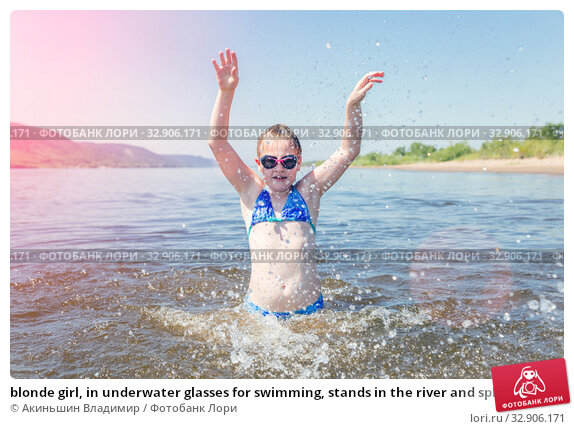 blonde girl, in underwater glasses for swimming, stands in the river and splashes water on a hot summer day. Стоковое фото, фотограф Акиньшин Владимир / Фотобанк Лори