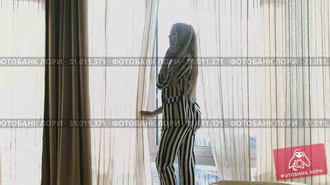 Купить «Blonde in a striped suit and black heels gets up from a soft puff and approaches the window», видеоролик № 31011371, снято 3 августа 2020 г. (c) Denis Mishchenko / Фотобанк Лори