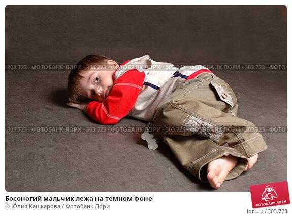 Босоногий мальчик лежа на темном фоне, фото № 303723, снято 23 марта 2008 г. (c) Юлия Кашкарова / Фотобанк Лори