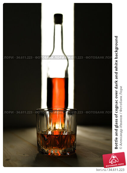 Bottle and glass of cognac over dark and white background. Стоковое фото, фотограф Александр Иванов / Фотобанк Лори