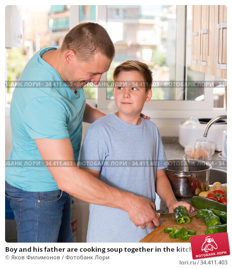 Boy and his father are cooking soup together in the kitchen. Стоковое фото, фотограф Яков Филимонов / Фотобанк Лори