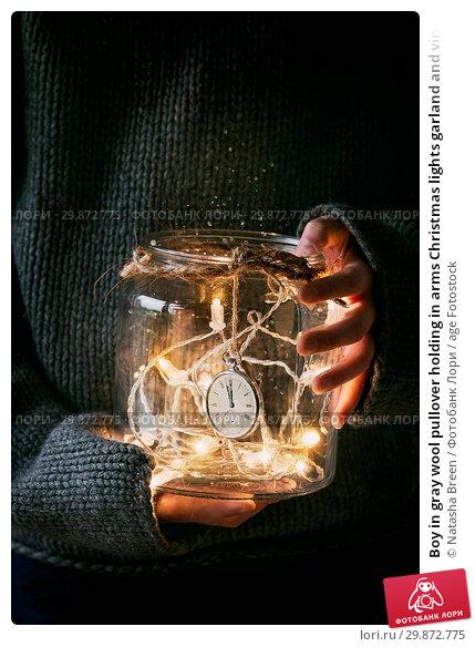 Купить «Boy in gray wool pullover holding in arms Christmas lights garland and vintage clock at 12 in glass jar. Christmas holiday mood.», фото № 29872775, снято 14 декабря 2019 г. (c) age Fotostock / Фотобанк Лори