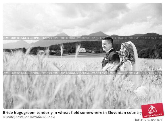 Bride hugs groom tenderly in wheat field somewhere in Slovenian countryside. Стоковое фото, фотограф Matej Kastelic / Фотобанк Лори