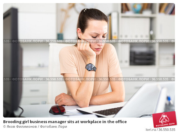 Brooding girl business manager sits at workplace in the office. Стоковое фото, фотограф Яков Филимонов / Фотобанк Лори