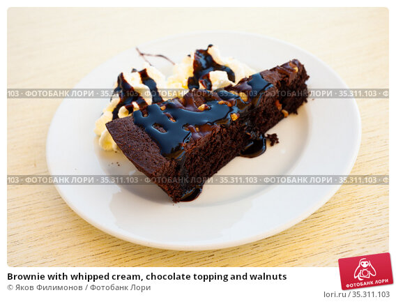 Brownie with whipped cream, chocolate topping and walnuts. Стоковое фото, фотограф Яков Филимонов / Фотобанк Лори