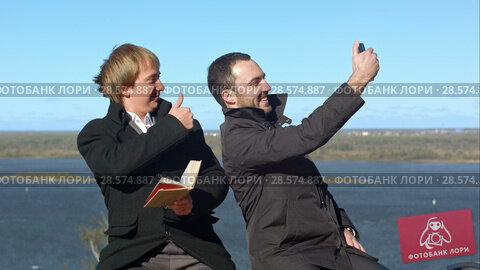 Купить «Busineeman giving thumb-up and making selfies on the bench outdoors.», видеоролик № 28574887, снято 11 октября 2015 г. (c) Vasily Alexandrovich Gronskiy / Фотобанк Лори