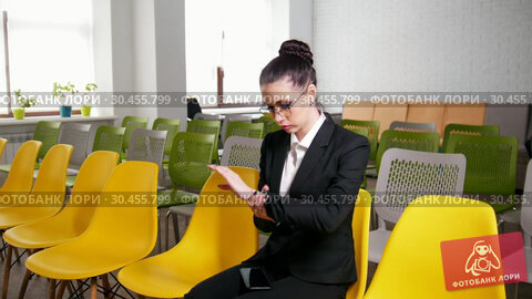Business concept. A woman sits in the business centre and getting nervous before the interview. Looking at her wrist to see the time but there is no watch. Стоковое видео, видеограф Константин Шишкин / Фотобанк Лори