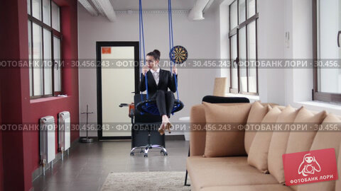 Business concept. A woman sitting on the swings in the office. Стоковое видео, видеограф Константин Шишкин / Фотобанк Лори