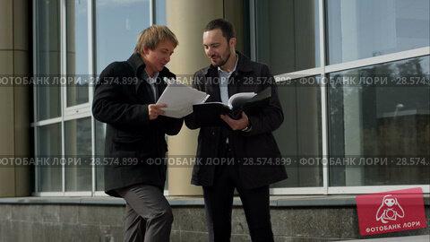 Купить «Business team discussing papers outdoor», видеоролик № 28574899, снято 10 октября 2015 г. (c) Vasily Alexandrovich Gronskiy / Фотобанк Лори