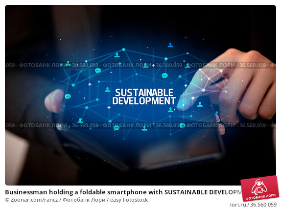 Businessman holding a foldable smartphone with SUSTAINABLE DEVELOPMENT... Стоковое фото, фотограф Zoonar.com/rancz / easy Fotostock / Фотобанк Лори